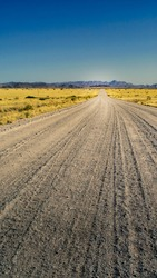 Desert gravel road with vanishing point displaying the way forward. 9:16 smartphone format or vertical banner. Beauty in nature