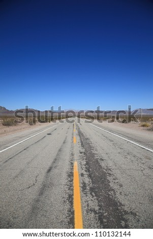 Desert Highway - Road stretching to horizon in Southwestern United States. With blue sky background and copy space.