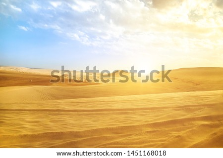 Desert landscape sand dunes at sunset sky near Qatar and Saudi Arabia. Khor Al Udeid, Persian Gulf, Middle East. Discovery and adventure travel concept. Sunlight over the desert dunes.