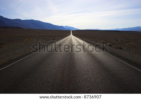 Desert road going through mineral deposits and geological formations of Death Valley National Park