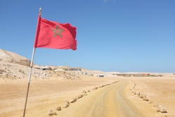 Desert Road with Moroccan Flag in Western Sahara Leading to Tourist Resort