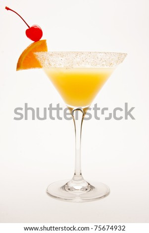 Desert Sand Tequila Sunrise Cocktail against a white background garnished with a cherry and orange wedge.