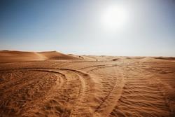 Desert scenic landscape of orange sand with vehicle traces and setting sun, wild nature of Dubai, UAE
