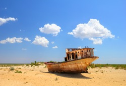 Desert scenic view of a dried Aral Sea (Aralkum) with old abandoned boat against the background of bright blue sky around Moynaq, (Muynak or Moynoq), Nukus, Karakalpakstan, Uzbekistan, Central Asia