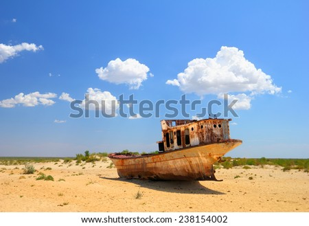 Desert scenic view of a dried Aral Sea (Aralkum) with old abandoned boat against the background of bright blue sky around Moynaq, (Muynak or Moynoq), Nukus, Karakalpakstan, Uzbekistan, Central Asia  #238154002