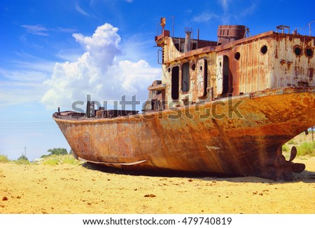 Desert scenic view of a dried Aral Sea (Aralkum) with old abandoned boat against the background of bright blue sky with cloud and yellow sand around Moynaq, (Muynak, Moynoq), Uzbekistan, Central Asia #479740819