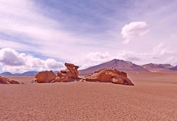 Desert volcanic stones and rocks. Crocodile stone. Vast extreme arid terrain. Andes volcano mountain landscape in South America. Clouds sky. Dry climate. Surreal landscape. Loneliness. Extreme terrain