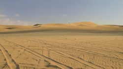 Desert with dunes and sand-hills at sunrise sunset hour, scenic landscape. Buggy tour in Huacachina, Ica, Peru. Extreme sports, adventure, journey and travel concept. Wide angle fish eye shot.