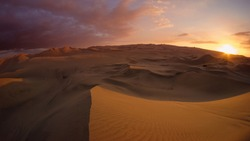 Desert with dunes and sand hills at sunrise sunset hour, scenic landscape. Buggy tour in Huacachina, Ica, Peru. Extreme sports, adventure, journey and travel concept. Wide angle fish eye shot.