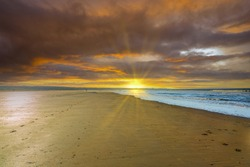 Deserted beach during sunset with orange deep blue colored clouds and low sun with sun rays on the horizon shining over the beach