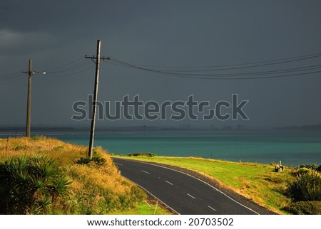 Deserted country road under stormy sky in New Zealand
