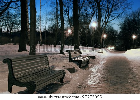 Deserted park in the evening, the benches, burning lanterns with rays of light, snow, winter. A city Landscape.