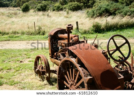 Deserted rusting vintage tractor on farm.