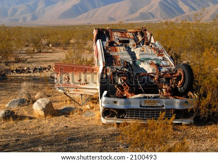 Deserted wrecked car in the desert with bullet holes in the door