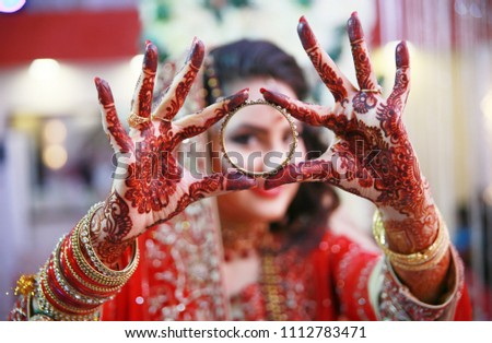 Desi Bride showing her henna hands wearing bangles on her wedding day - Shutterstock ID 1112783471
