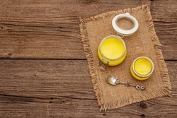 Desi ghee (ghi), clarified melted butter. Healthy fats bulletproof diet concept or paleo style plan. Glass jars, silver spoon on vintage sackcloth. Wooden boards background, copy space, top view