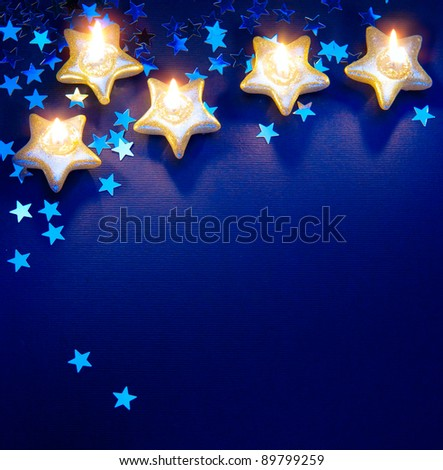 Design a background for the Christmas greetings card with candles on a blue background - stock photo