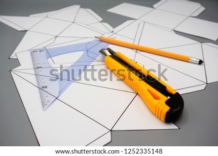 Design and engineering. Building and construction. Professional workplace with three dimensional figures unfolded ruler, pen and cutter .