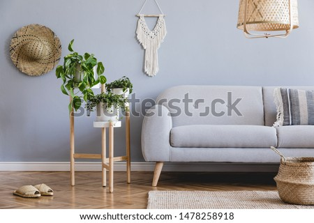 Design bohemian composition of living room interior with gray sofa, wooden flowerbed, beige macrame, rattan lamp ,plants, basket and elegant accessories. Stylish and minimalistic home decor. Template.