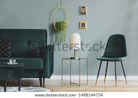 Design composition of living room interior with green vlvet sofa, stylish coffee table, marble table lamp, pouf, pillows, hanging flowerbed, plants and elegant accessories. Modern home decor. Template