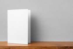Design concept - front view of greeting card on bookshelf and grey wall for mockup, not 3D render