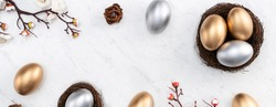 Design concept of Golden and silver Easter eggs in the nest with white plum flower on bright marble white table background.