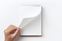 Design concept - Perspective view brown hardcover spiral notebook, man's hand flip curl page isolated on background for mockup