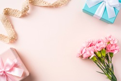 Design concept - top view of a bunch of carnation, gift box and vintage ribbon on pink background for mother day mockup