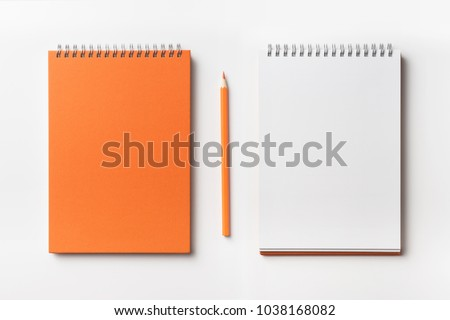 Design concept - Top view of orange spiral notebook and color pencil collection isolated on white background for mockup #1038168082