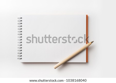 Design concept - Top view of orange spiral notebook and wooden ballpoint pen isolated on white background for mockup