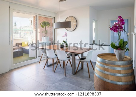 Design dining room with orchids and terrace. Nobody inside
