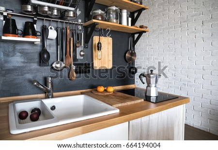 Design of a modern home kitchen in the attic and rustic style. Black wall with shelves, trays, jars, mugs, sink. In the background a wall of white brick.