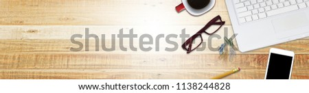 Design of standard banner office black work desk table with laptop, tablet, cup of coffee and black smartphone on wood Backgrounds