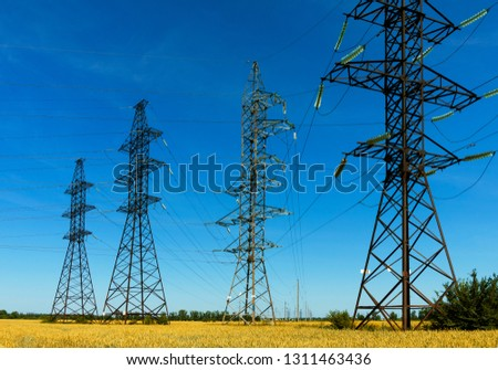 design of transmission line, transmission line, high voltage tower in a field on the background of clear blue sky. Industrial landscape. #1311463436