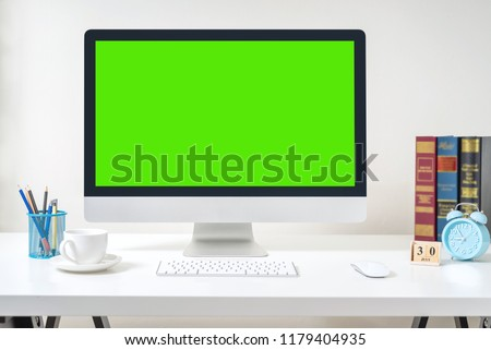 Design of workplace with computer green screen is standing on a desk in an office, Business Concept, copy space.