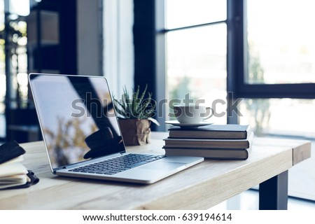 design of workplace with laptop and cup of coffee in home office