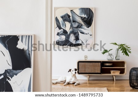 Design scandi home interior of living room with wooden commode, gray sofa, black rattan pouf, plant and elegant accessories. Stylish home decor. Mock up abstract paintings.  Dog is lying on the carpet