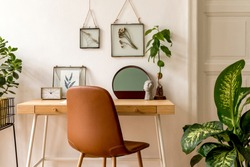 Design scandinavian interior of home office space with a lot of mock up photo frames, wooden desk, a lot of plants, mirror, office and personal accessories. Stylish neutral home staging. Template.