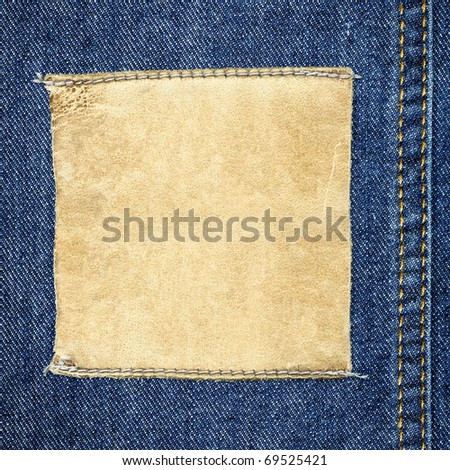 Designed background for your text - detailed closeup of blank grungy scratched leather label on blue denim, square