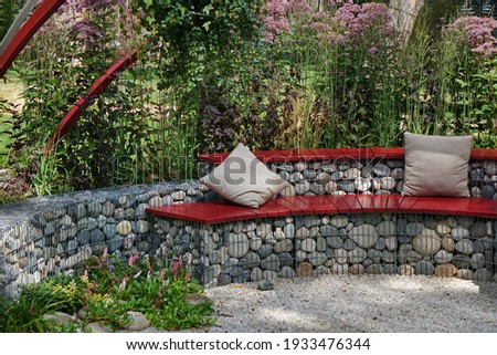 Designed Backyard Garden Patio and Outdoor Party Place. Modern Garden Design and Landscaping. Round Bench Made from Gabions with Wooden Seat. Landscaped Family Resting Area with Fireplace. Stock photo ©