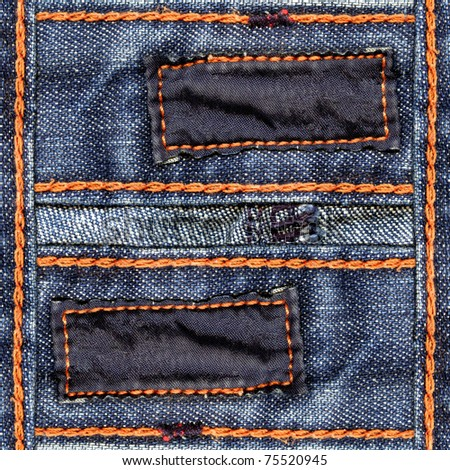 Designed blue jeans background with two blank dark cotton labels and orange seams' threads
