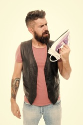 Designed for a maximum glide. Hipster looking at electric ironing tool. Unshaven brutal man with steam iron in hand. Household ironing. Bearded man holding clothes iron. Providing household services.