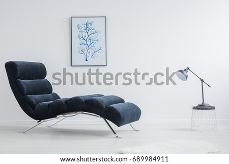 Designed small table with black lamp stands against modern chaise lounge Foto stock ©
