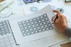 Designer designing drawing sketch pattern geometric flower seamless wallpaper fabric textile fashion industry ceramic. artistic design studio.