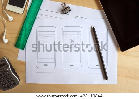 Designer desk with paper prototype of a mobile application. Flat lay.