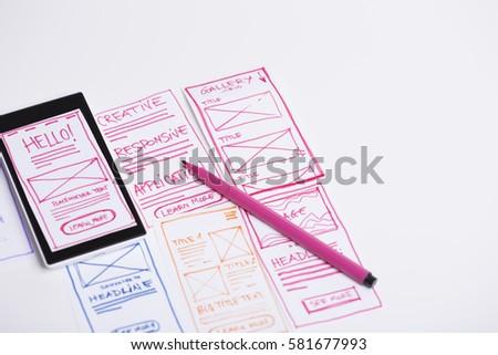 Designer desk with paper sketches for mobile website layout. Website, mobile application, prototyping