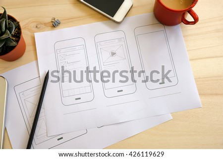Designer desk with UI wireframe sketches. View from above