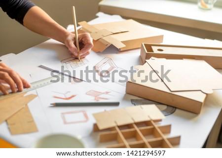 Designer draws a mockup for crafting cardboard box. Development of packaging design sketch. #1421294597
