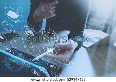 Designer hand using mobile payments online shopping,omni channel,in modern office wooden desk,icons graphic interface screen,eyeglass,filter