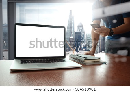 designer hand working and smart phone and blank screen laptop on wooden desk in office with london city background